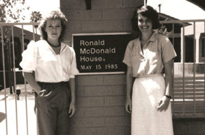 Two women, the original staff of RMHC Phoenix, stand in front of the Roanoke House dedication plaque