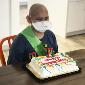 Boy smiles in the kitchen with his birthday cake