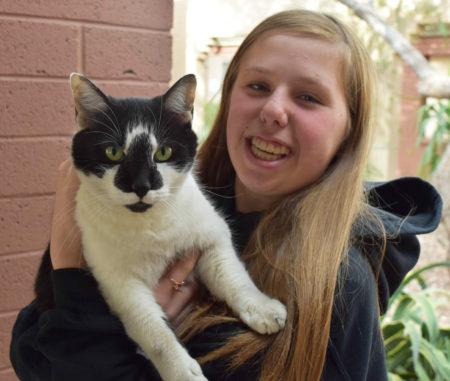 Teenage girl holds Smokey the housecat