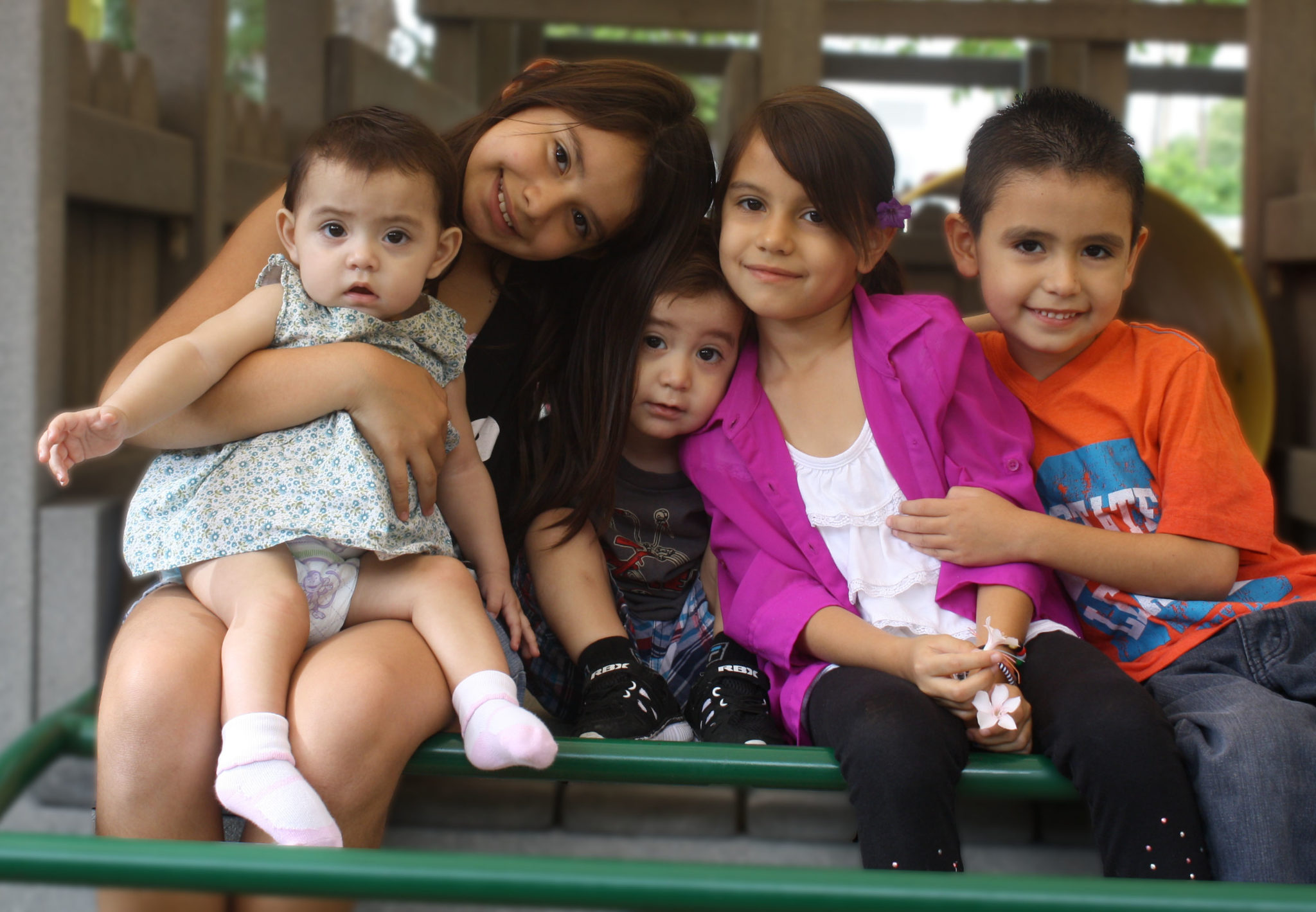 Four siblings posing in a hug on the RMHC playground