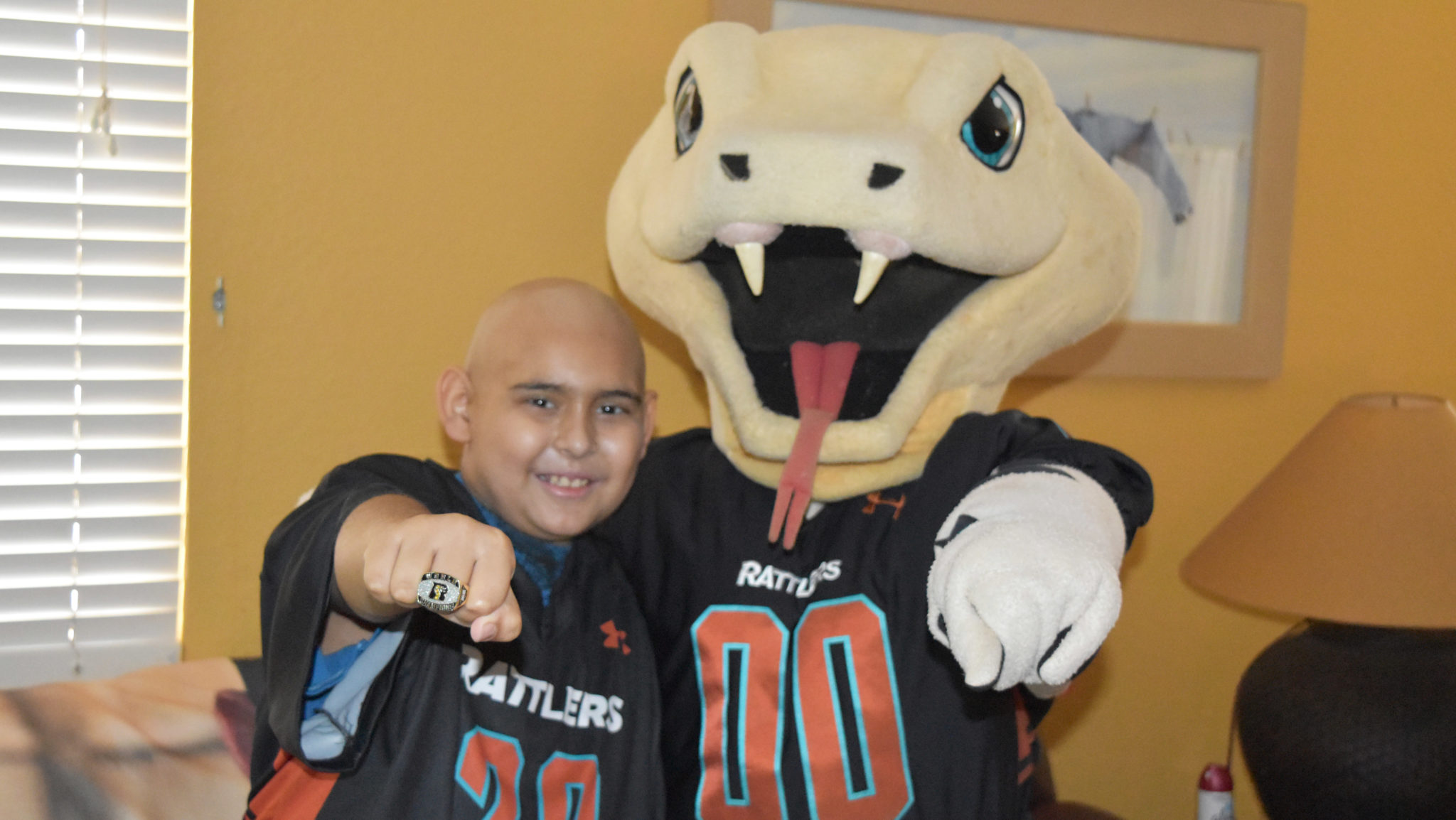Teenage boy poses with the Arizona Rattlers' mascot