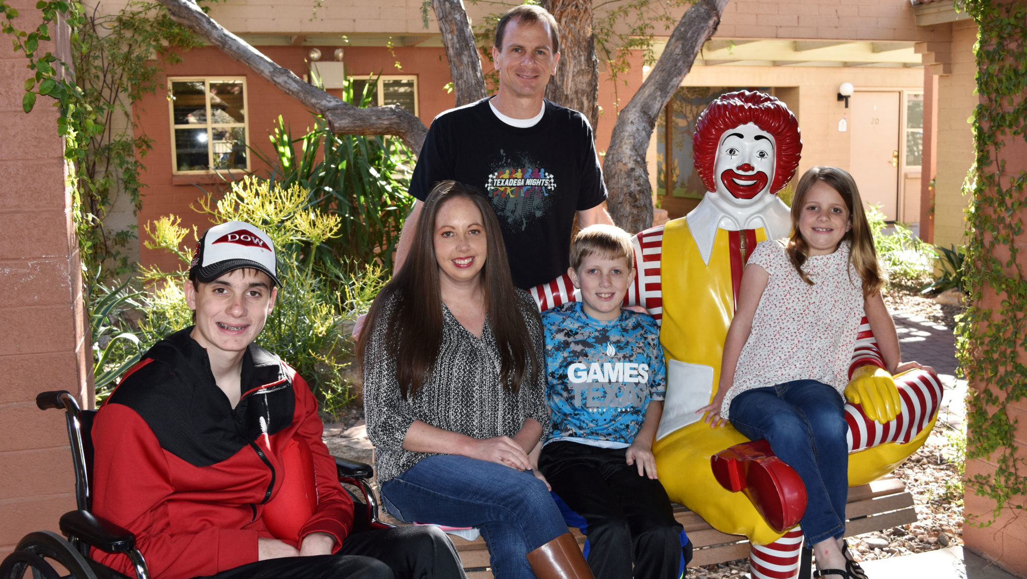 Family of 5 poses on the Ronald McDonald bench