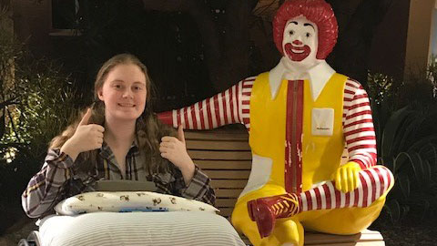 Teenager in a wheelchair posting next to the Ronald McDonald statue