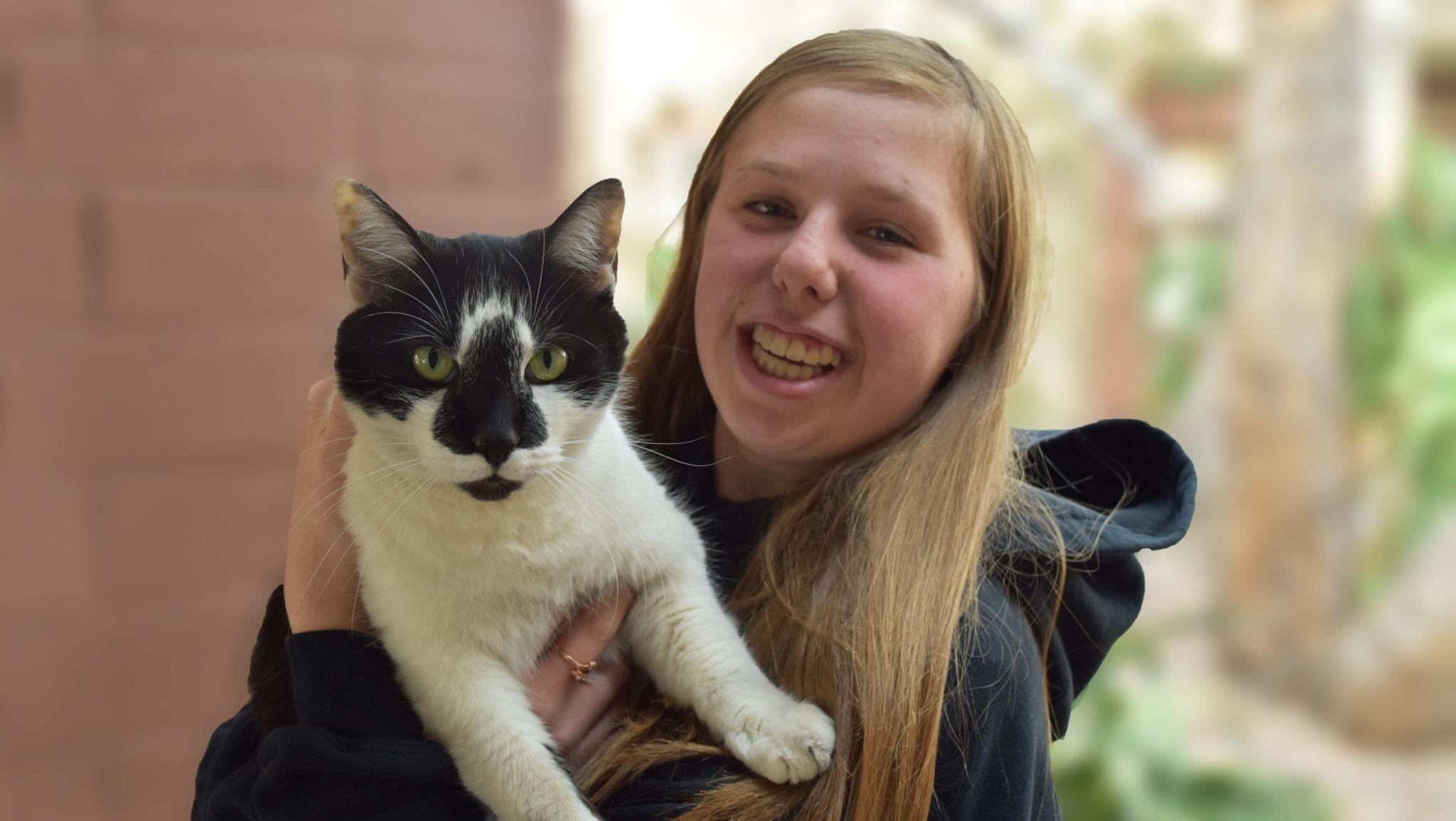 Teenage girl holding the House cat Smokey