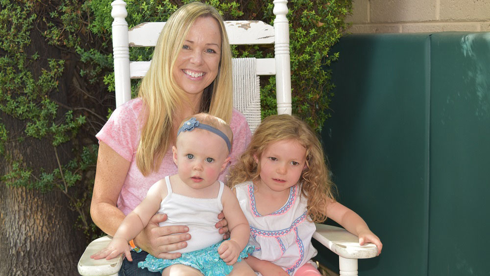 Mother sits in a rocking chair with her two daughters on her lap