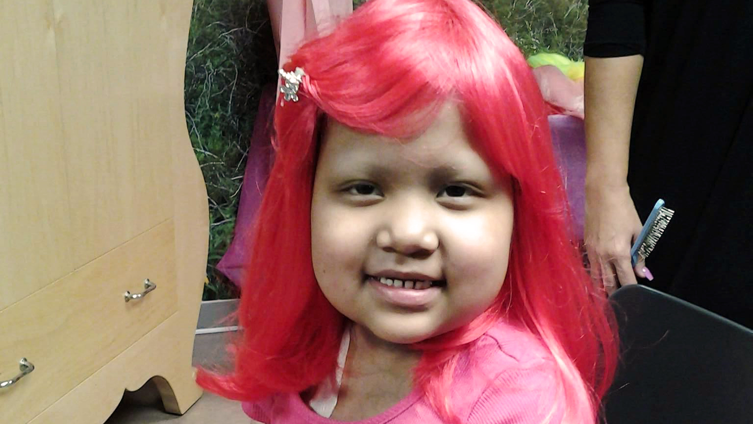 Girl with a bright pink wig poses for a photo