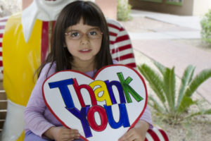 "Little girl sitting on the Ronald McDonald bench holding a sign that says ""thank you"""