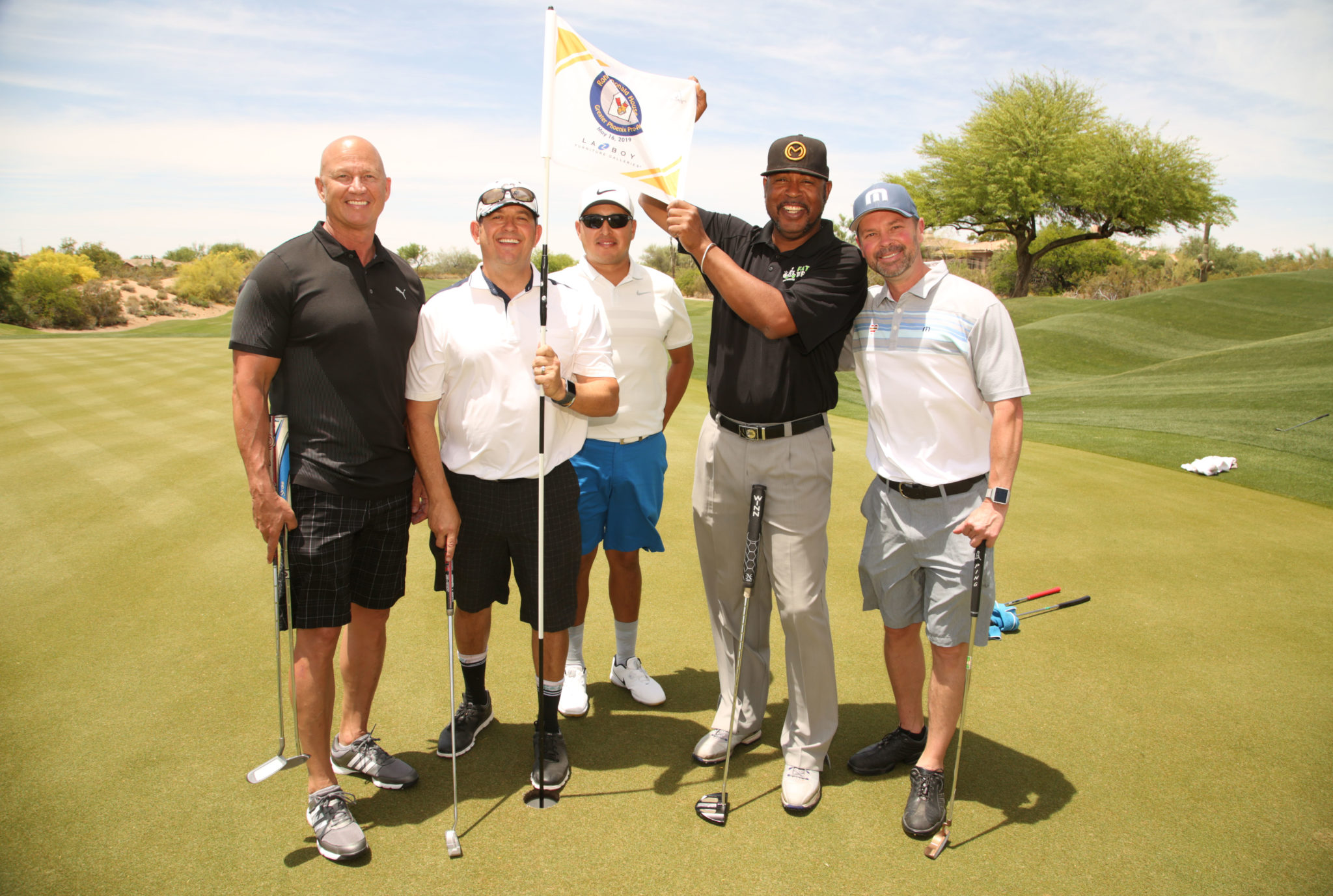 Golfers stand on the green of the Greater Phoenix Pro-Am