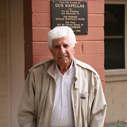 Gus Kapellas in front of the garden plaque