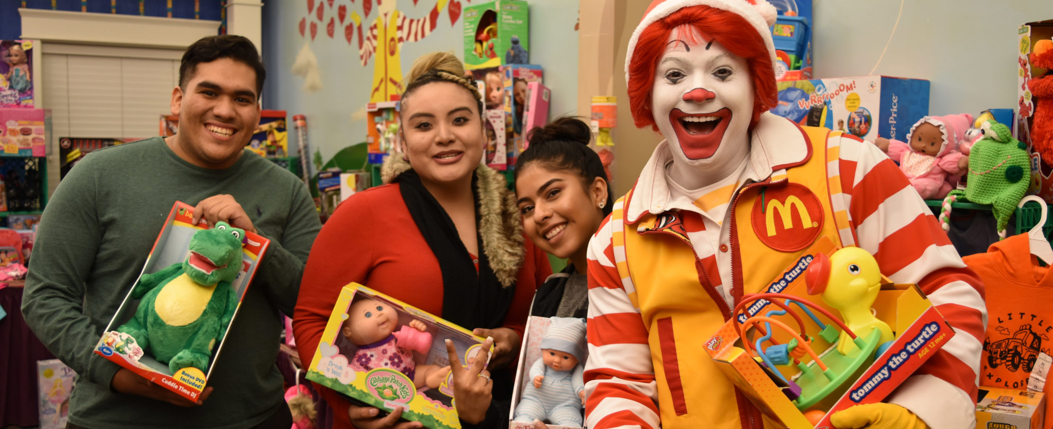 Ronald McDonald and three volunteers with donated toys