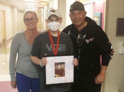 Mom, dad, and son pose for a picture in the hospital