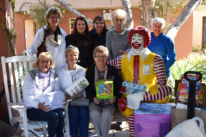 Group of women sit on the Ronald McDonald bench with in-kind donations they brought