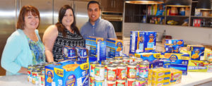 Three RMHC supporters with donated food items