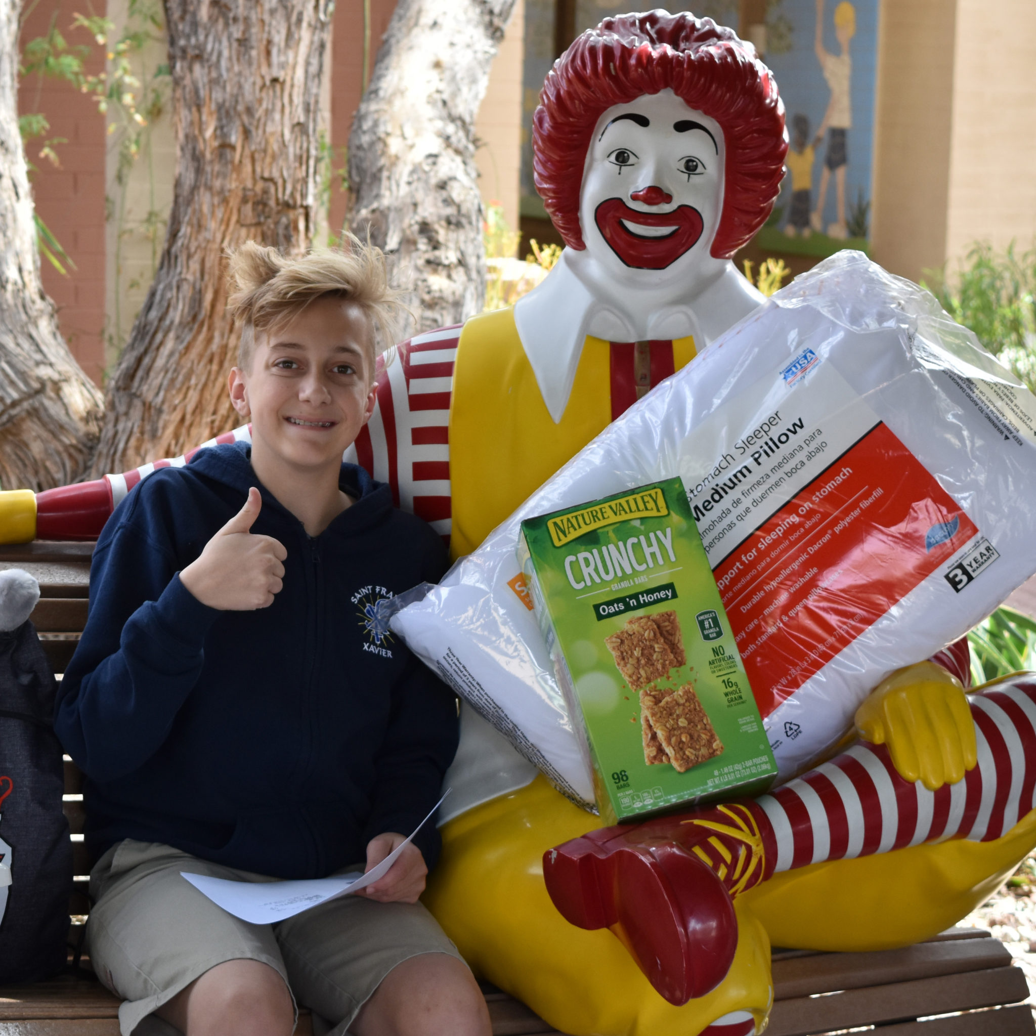 Tennage boy posing on the Ronald McDonald bench with donated items