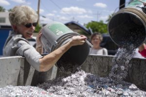 Woman pouring pop tabs into a large container