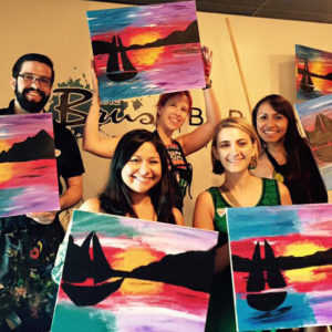Group of Red Shoe Members pose with paintings they made at a Brush Bar fundraiser