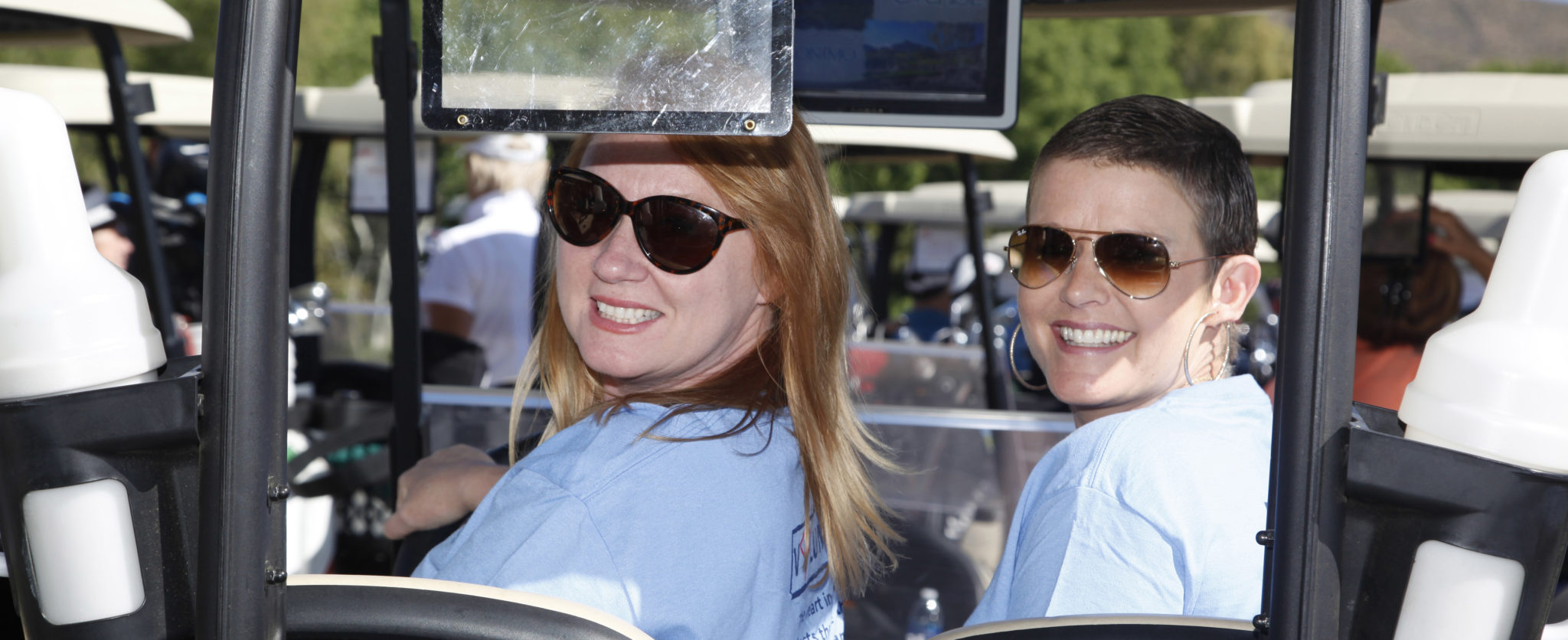 Two female volunteers pose in a golf cart
