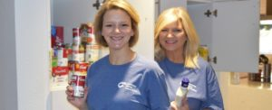 Two female volunteers organize the pantry in the kitchen
