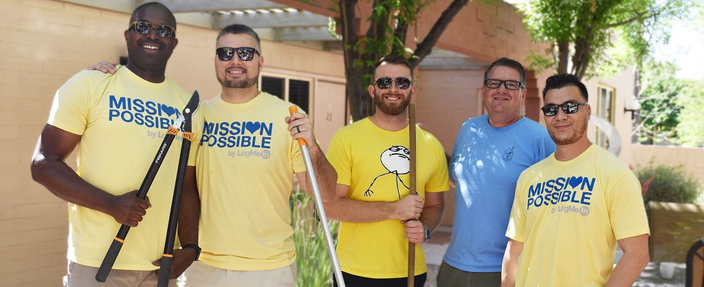 Group of 5 men pose with yard tools during a volunteer project