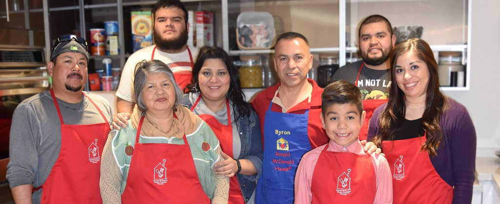 A family of volunteers pose in their RMHC aprons in the RMHC kitchen during dinner