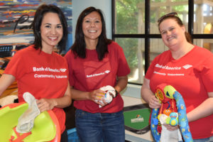 Volunteers from Bank of America clean toys in the playroom